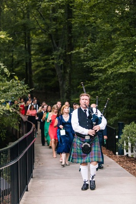 Bagpiper in kilt and Scottish clothing plays bagpipes to lead wedding guests to reception site