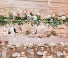 Tall wedding centerpiece at wedding reception clear vase, green leaves, pink rose, white hydrangea