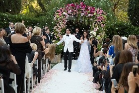 Bride and groom walking up aisle as husband and wife flower petal cannon going off white petals