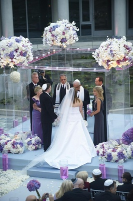 Bride and groom with parents under clear ceremony structure