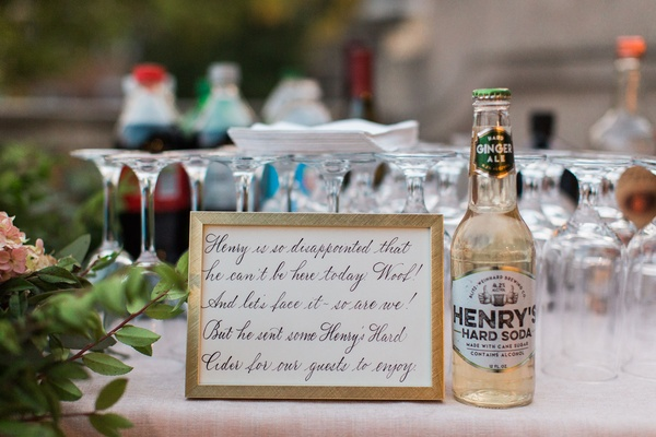Henry's hard soda wedding reception cocktail hour with calligraphy sign honoring dog puppy