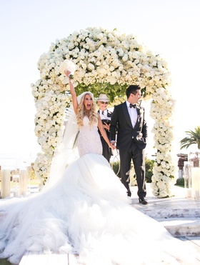 Bride in galia lahav mermaid wedding dress with groom after being pronounced husband and wife arch