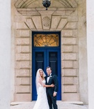 Bride in Anne Barge wedding dress and veil and groom in tuxedo and bow tie in front of blue door