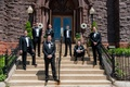 Groom and friends standing on stone steps