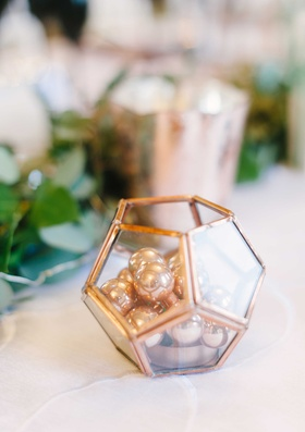 a small copper geometric terrarium item filled with small beads on a reception table