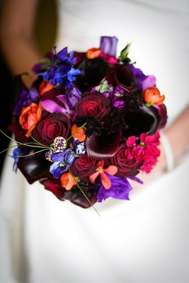 bouquet with red, blue, purple, pink, and orange flowers and jeweled pin