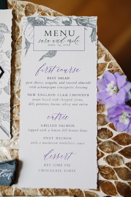 wedding reception menu with printed grey flowers and purple details