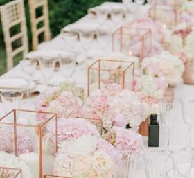 Wedding reception long centerpiece mini rose arrangements candle votives rose gold vessels geometric