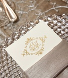 Menu card on ivory stationery with gold script monogram inside napkin on crystal charger
