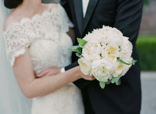 bride wearing lace off the shoulder dress holding white bouquet