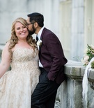 Bride in gold wedding dress Amsale and groom in glasses and burgundy plum suit jacket bouquet
