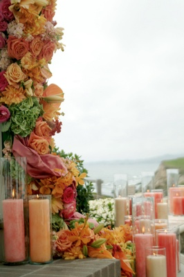 Orange and white candles decorate a gazebo for a wedding