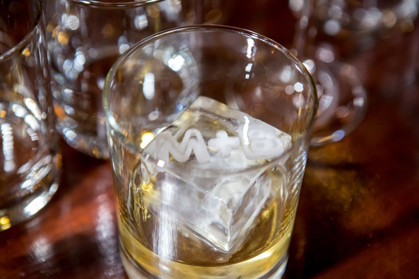 Wedding reception alcohol in glass with square ice cube large with monogram carved into side