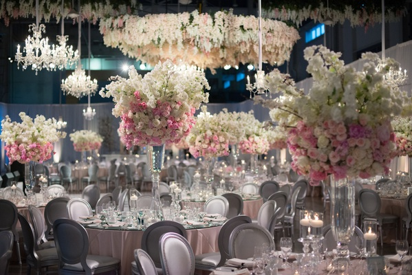 Wedding reception with wisteria flower chandelier over dance floor and tall centerpieces every table