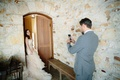 groom in grey suit takes photo on his phone of the bride in a ruffled blush wedding dress
