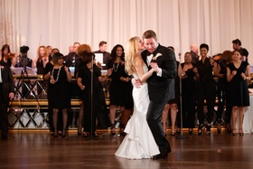 Bride in a strapless Pnina Tornai dress dances with groom in black tuxedo