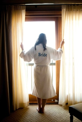 Bride stands at window in hotel room with white robe
