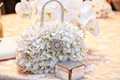 white floral purse with silver metallic box on white table linens