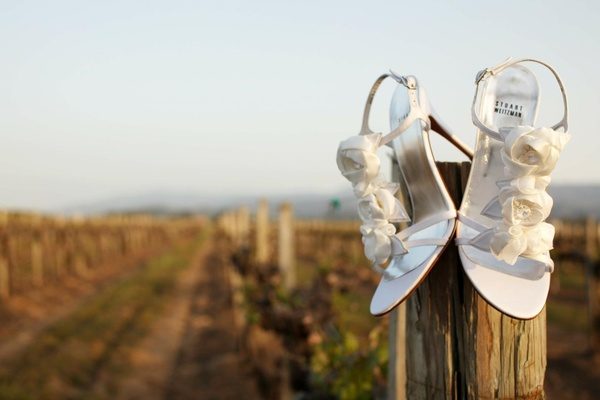 Stuart Weitzman bridal shoes on vineyard fence