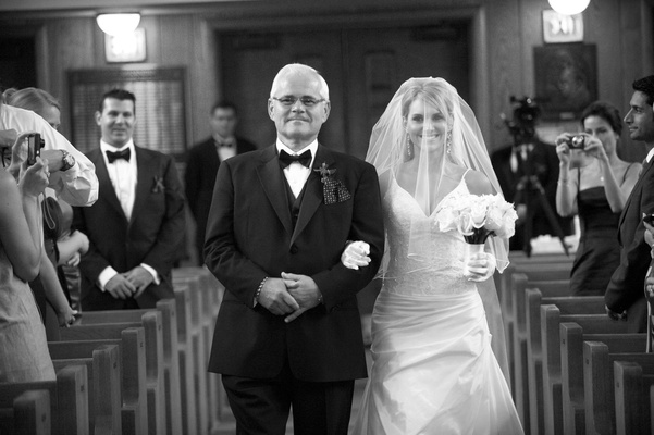 Black and white photo of father of the bride walking her down the aisle