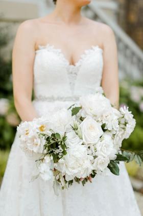bride in strapless lace romona keveza wedding dress holding white peony rose ranunculus bouquet
