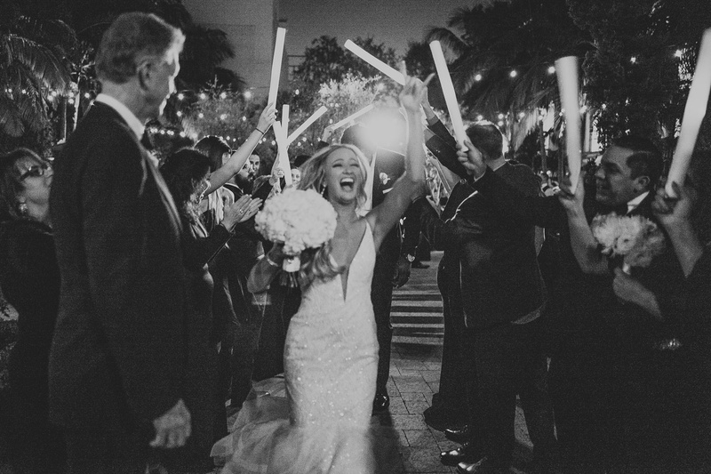 black and white photo of bride with bouquet as guests wave neon light up sticks celebration