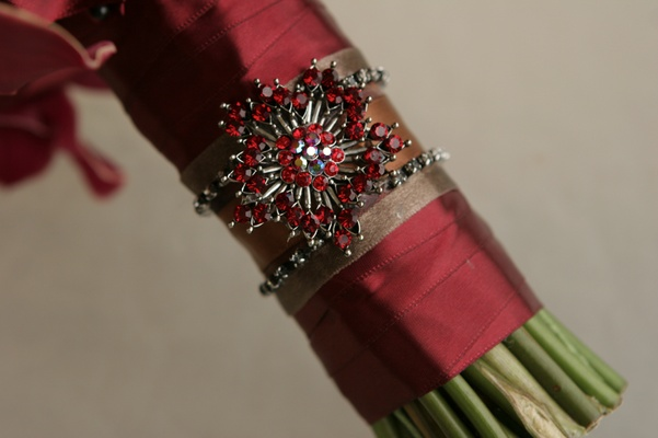Red ribbon around bouquet stems and jewel brooch
