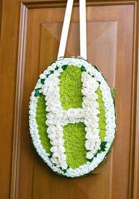 Oval flower sign with initial made of roses on ceremony door