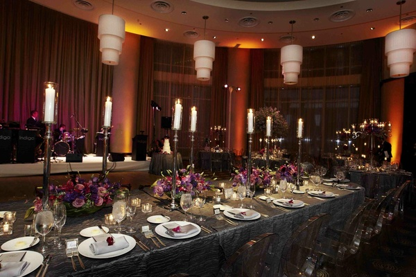 Grey linens at wedding reception with purple flowers