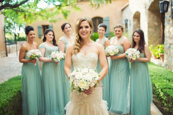 Bride in strapless Liancarlo mermaid wedding dress with bridesmaids in mismatched mint green gowns