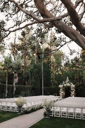 wedding ceremony white chairs white flowers greenery lights hanging from trees twinkle lights string