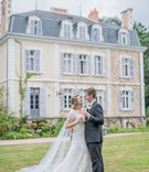 bride in short sleeve oleg cassini wedding dress champagne flute in front of french wedding venue