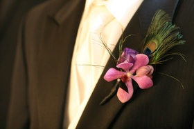 Groom wearing pink flower and feathers on lapel