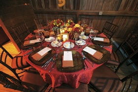 Red table at barn wedding with fall wedding flowers
