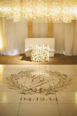 Wedding reception sweetheart table composed of white flowers, dance floor with couple's monogram