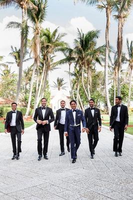 wedding party groomsmen in tuxedos groom in navy blue tuxedo walking down path in palm beach hotel