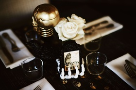 wedding reception skeleton hand holding beware sign gold skull white flowers