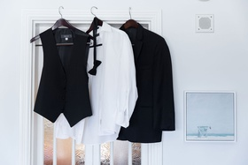 wedding attire for groom on hangers in groom's suite casa del bar black tuxedo vest bow tie shirt