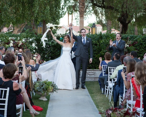 Outdoor wedding ceremony at La Quinta Resort & Club Palm Springs area a line gown guests taking pics