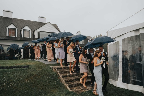 wedding guests walking down stairs with umbrellas into tented wedding venue family home