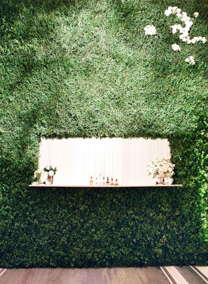 Wedding bar with alcohol displayed and flower arrangements inside hedge wall at wedding