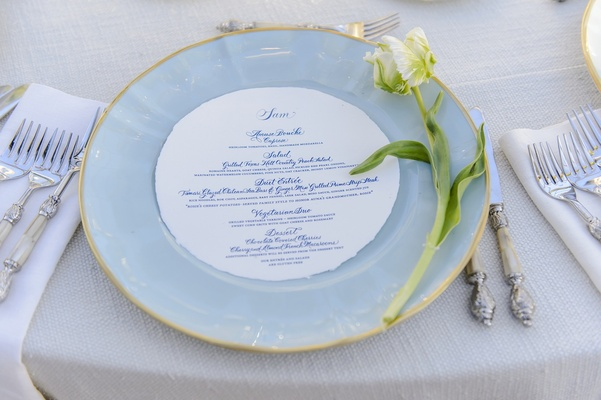 Gold-rim light blue plate with single tulip flower at wedding