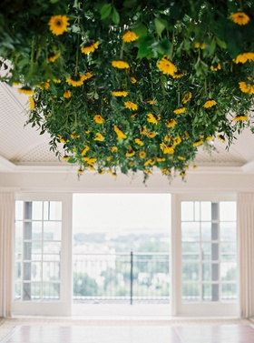 Wedding reception in Washington DC sunflowers and greenery leaves overhead above dance floor