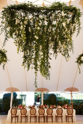 wedding reception tent long table wood chairs low centerpiece floral chandelier greenery