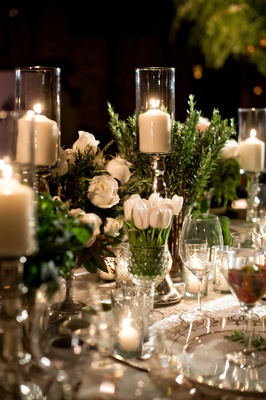 tablescape with vases of white roses, white tulips, and candles