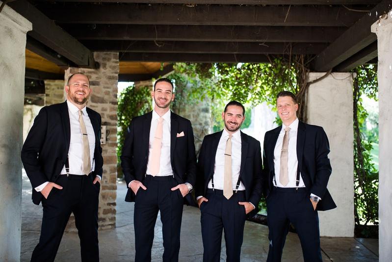 groom in pink tie groomsmen in suits suspenders champagne tie tie clips hands in pockets