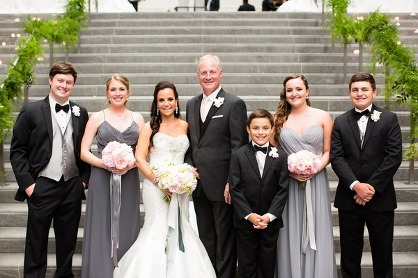 bride and groom with their respective sons daughters gray dresses charcoal tuxedos bouquets