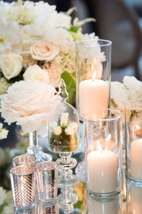 centerpieces with candles in hurricanes, mercury votes mirror table reception