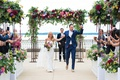 groom holding bride's hand and pumping fist after ceremony ending, with colorful florals