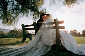 bride and groom kiss seated on park bench